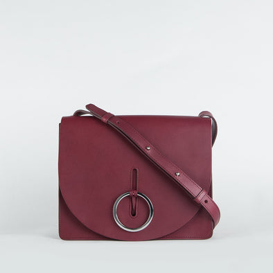 Women's minimalist geometrical shoulder bag in black chemical-free leather body, embellished with a silver hoop.
