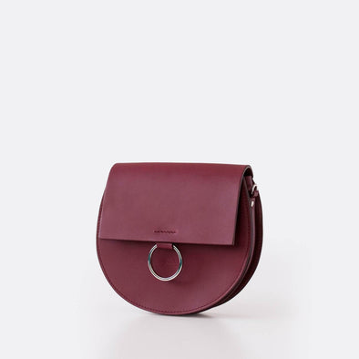 Round waist bag in burgundy leather.