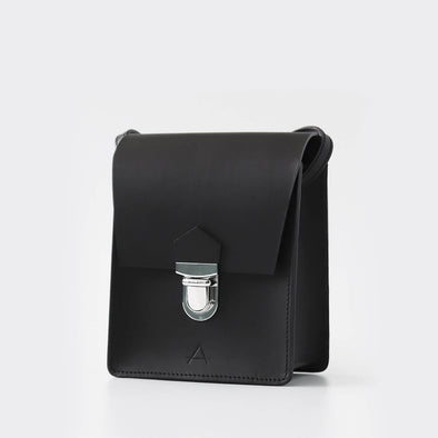 Minimalist cubo shoulder bag in black chemical-free leather.