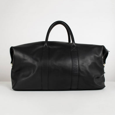 Black leather duffle bag with detachable shoulder strap, two top handles, golden hardware with leather zip pulls, and buckled leather tag.
