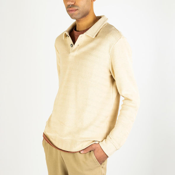 Beige sweat with two big brown buttons at the collar.