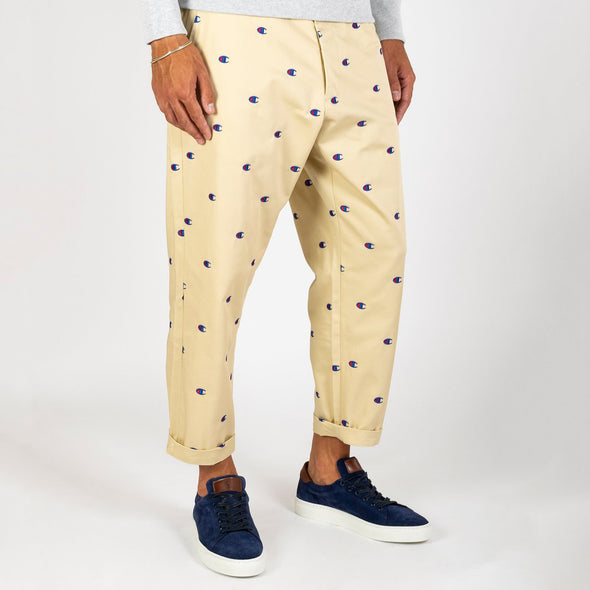 Champion x Beams beige chino pants with logo print.