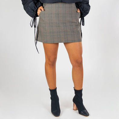 Preppy plaid mini skirt with side pockets, woven logo label at the side, and back zipper closure.