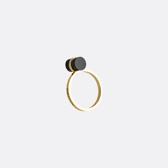 Golden ring with black cylindrical detail.