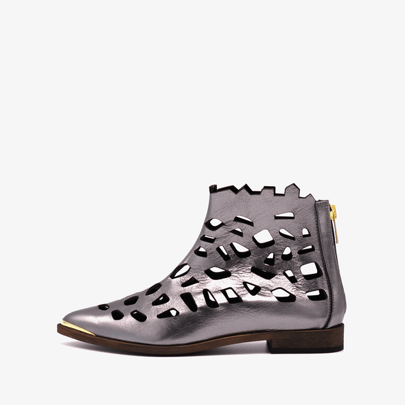 Perforated leather bronze flat ankle boots with golden details.