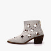 White heeled boots in perforated leather with star-shaped cutouts.