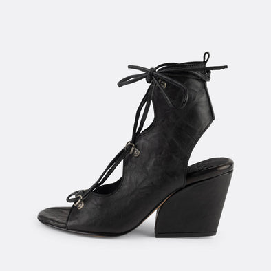 Black leather heeled sandals with straps to tie around the ankle.