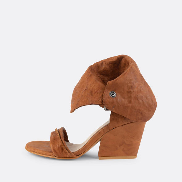 Brown leather heeled sandals with an ankle band.