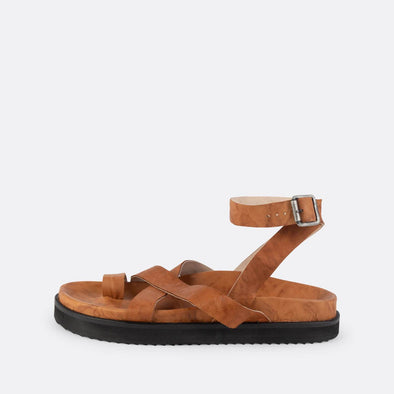 Brown leather slipper sandals with ankle and toe straps.