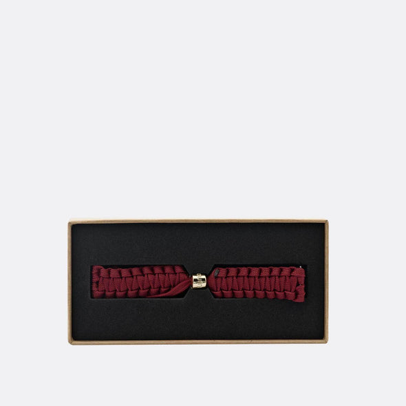 Burgundy paracord braided strap with gold clasp.