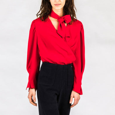 Red blouse with straps to tie at the neck.