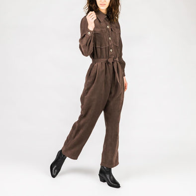 Dark brown jumpsuit with long sleeves and a belt to tie at the waist.