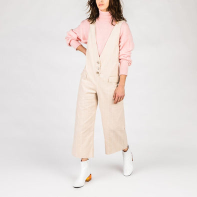 Light pink corduroy jumpsuit with button placket.