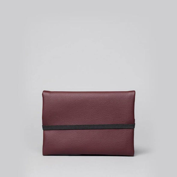 Unisex essential pouch in bordeaux vegan leather.
