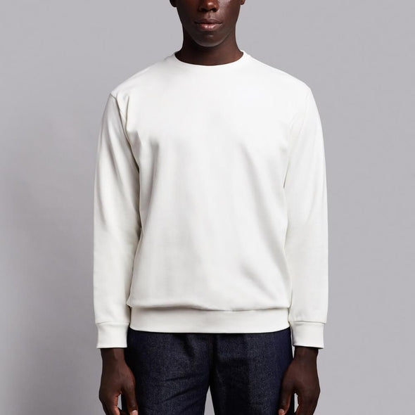 White crewneck sweatshirt with white embroidery on the chest.