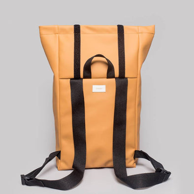 Unisex water resistant roll–top backpack in honey vegan leather.