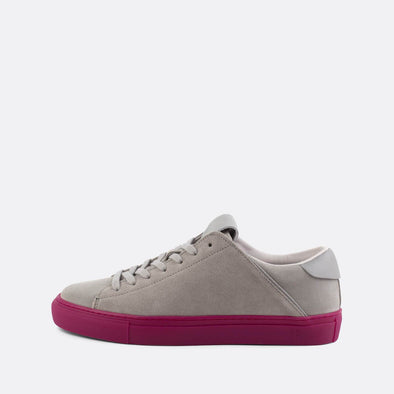 Minimalist grey suede low-top sneakers with a distinct lilac sole.