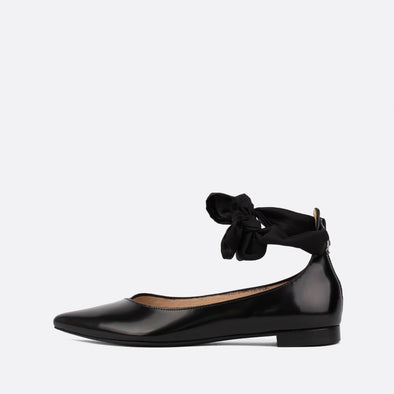 Black leather ballerinas with fabric strap to tie at the ankle.