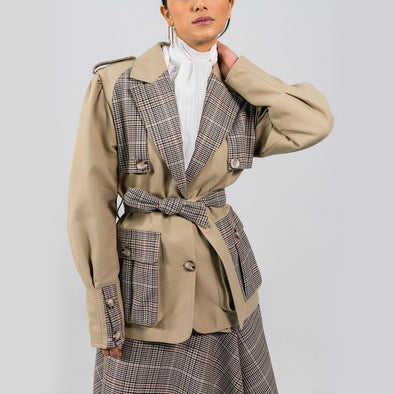 Safari jacket with plaid in black and beige tones and sash belt wrapping around the waist with large utilitarian pockets.