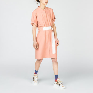 Soft pink dress with a white d-ring belt at the waist.