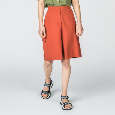 Rust high-waisted longline shorts with cargo pockets.
