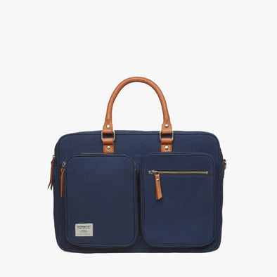 Rectangular style suitcase in denim blue cordura textile with two rectangular exterior pockets, camel brown leather handle and leather zip tabs, silver zipper camel brwo nleather tabs