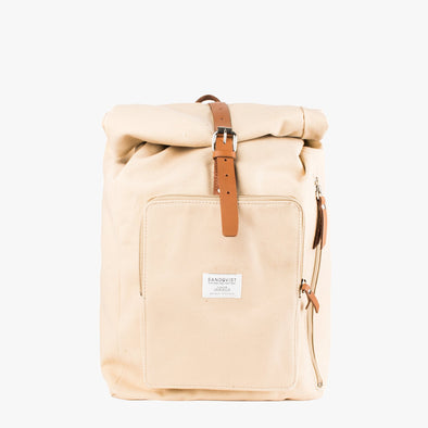 Light beige canvas backpack with a roll top, exterior pocket side zipper and two camel brown leather buckle straps