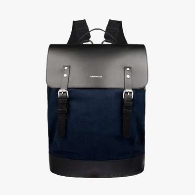 Minimalist boxy backpack innavy blue canvas with black leather flap and two buckle straps