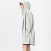 Unisex moon colored casual raincoat with double welded slanting pocket flaps, adjustable cuffs and a fishtail.