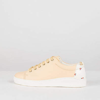 Low sneakers in pastel yellow leather with white rubber sole and tiny flower print on the heel