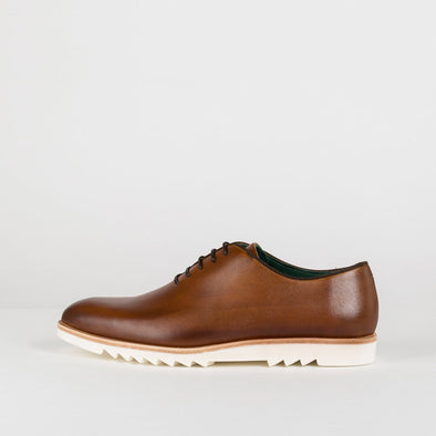 Man's brown polished leather oxford shoes with a distinct sole.