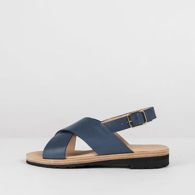 Minimalist sandals with crossed straps and ankle buckle in petrol blue leather with reinforced sole in leather and rubber