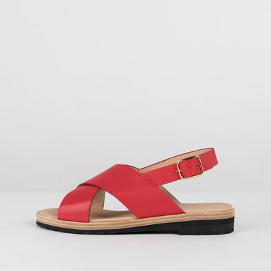 Minimalist sandals with crossed straps and ankle buckle in crimson red leather with reinforced sole in leather and rubber