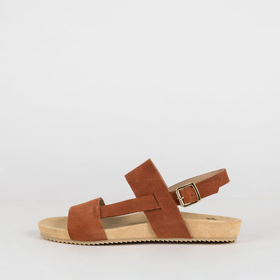 Brown suede flat sandals with a double-strap connected by a side-strap.