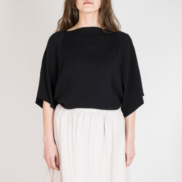 Oversized black t-shirt with raw edge, squared neckline and 3/4-length raglan sleeves.