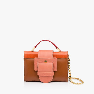 Structured mini bag in multi-colored leather, with camel brown body, orange glossy panel, large pastel pink buckle, red handle and detachable golden chain shoulder-strap
