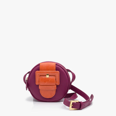 Circular shoulder bag in purple leather with large orange buckle