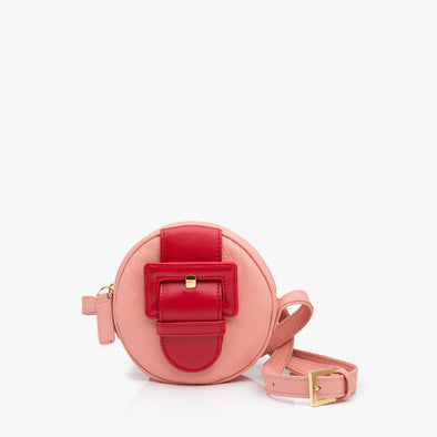 Circular shoulder bag in pastel pink leather with large red buckle