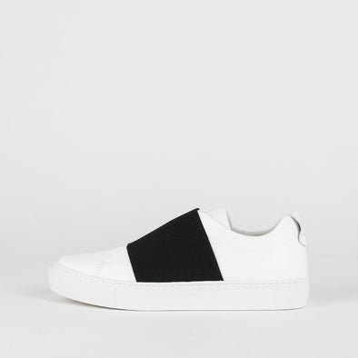 White leather sneakers with black elastic strap.