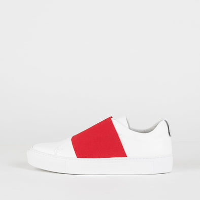 White leather sneakers with red elastic strap.