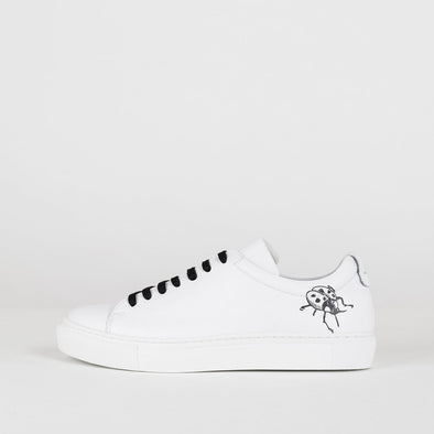White leather sneakers with black ladybug print on both sides.