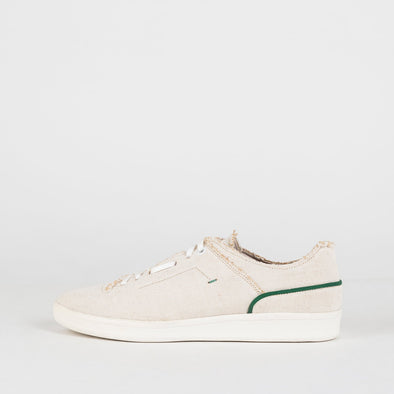 Sand colored canvas sneakers with a green line detail on both sides.