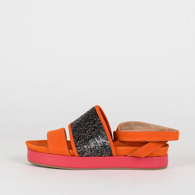 Vivid orange flat sandals with a pink sole and a strap with silver sequins.