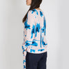 Fluid print top with long sleeves and knots the wrists.