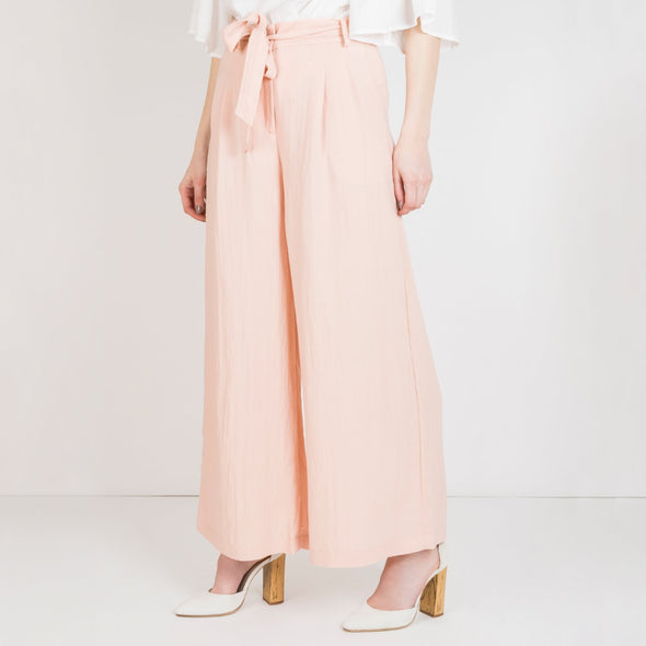 Fluid baby pink pants with a wide cut, pockets and a belt.