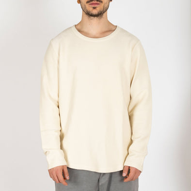 Off white crewneck sweater made from 100% cotton jersey.