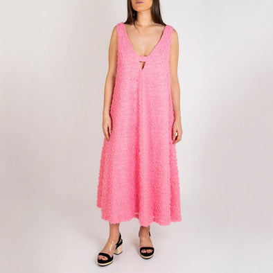 Light pink textured dress featuring a V-neck and V shaped detailing at the back.