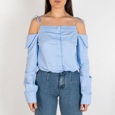 Light blue bodysuit with cut out shoulders tied up with a thin strap.