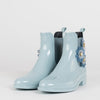 Baby blue chelsea-style rainboots in glossy synthetic material with three acrylic flower appliques on the side