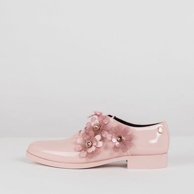 Baby pink oxford shoes in glossy synthetic with acrylic flower appliques on the side